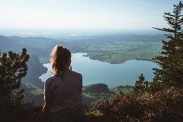 girl sitting on the edge overlooking the lake in the distance