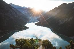 hiker overlooking lake lake while sun is rising