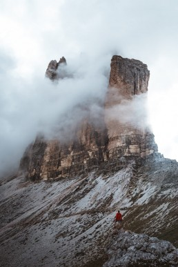 hiker standing in front of a huge mountainface