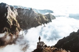 person standing on the edge looking on to a sea of fog