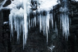 sharp icicles hanging down on a black wall