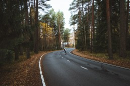 person skating along a road through the forest