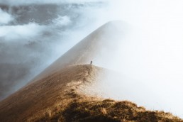 person standing on a ridge enclosed by fog