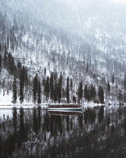 boat on a lake with a snowy hillside in the back