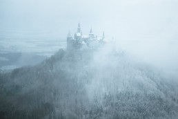 castle on the hill enclosed by fog