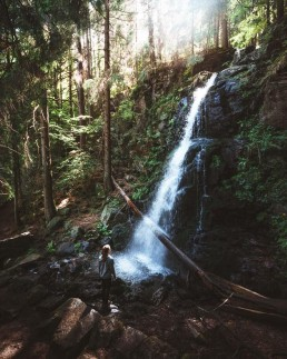 girl standing on a rock facing a waterfall