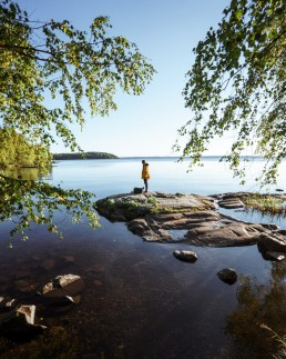 person standing centered on a rock on a lake