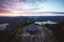 tent and campers on top of the mountain while sun is rising