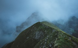 hiker standing on the ridge surrounded by fog in the blue hour