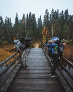 two hikers on a wooden bridge
