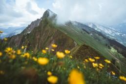 Wanderer steht auf dem Grat und schaut auf Felsen