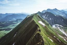 Grüner Berggrat mit Wanderer im Tageslicht