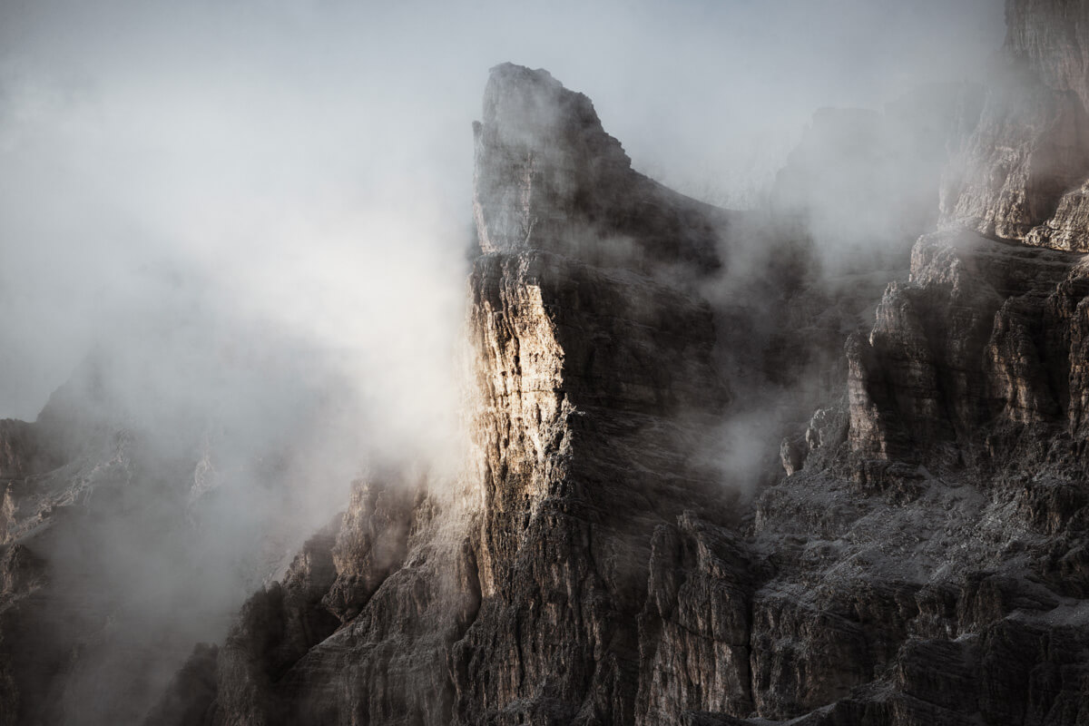 A rugged mountain peak gets illuminated by a sunray surrounded by fog